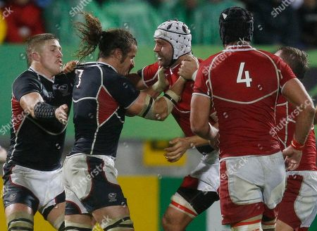 Todd Clever, second left, captain of the USA team and teammate Hayden Smith battle with Russia's Denis Anotonov, second right, during their Rugby World Cup game in New Plymouth, New Zealand