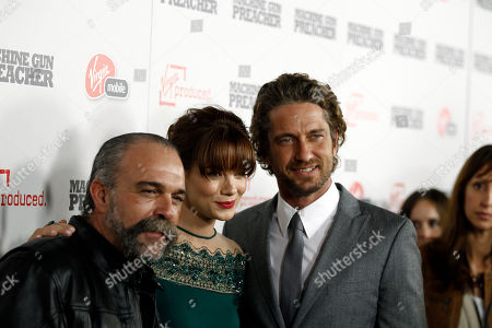 "Stock Image of Gerard Butler, Sam Childers, Michelle Monaghan Cast members Gerard Butler, right, Michelle Monaghan, center, and Sam Childers, whose life is the inspiration for the film and is portrayed by Butler, pose together at the premiere of ""Machine Gun Preacher"" in Beverly Hills, Calif., . ""Machine Gun Preacher"" opens in theaters Sept. 23, 2011"