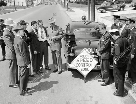 Stock Image of Visiting law officials observe how Columbus police use radar equipment in nabbing speeders and plotting traffic density in Columbus, Ohio on May 1, year unknown. At left are Lt. Herbert M. Miller, Des Moines, Iowa; Trooper E.P. Schroeder, Nebraska State Patrol; Capt. Kermit Lewis, Indiana State Police; Lt. Earl Smith, Indiana State Police; Capt. Robert Bates, Indianapolis police; and Capt. C.O. Layne, Texas Highway Patrol. On the right of the cruiser, left to right, are Capt. Andy Jacobs, Indianapolis police; A.J. Dufort, Columbus radar operator; Capt. B.P. Smith, Columbus office chief; Donald D. Cook, safety director; and police director Thomas Soully