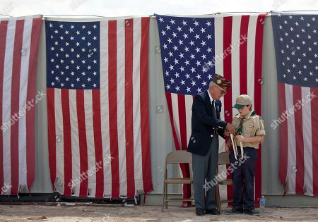 Retired Air Force Master Sgt. Kenny James, left, helps Michael Beck, of Las Vegas Boy Scout Troop 133, with his bugle during a 9/11 anniversary and flag retirement ceremony, in Pahrump, Nev