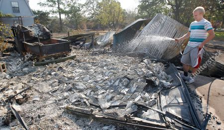 James Whitaker Garrett Quinn sprays water on hot spots at a neighbors home that burned when wildfires swept through the area, in Bastrop, Texas. More than 1,000 homes have burned in at least 57 wildfires across rain-starved Texas, officials said Tuesday