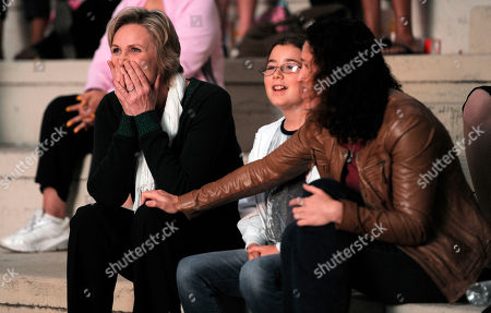 """Jane Lynch, Lara Embry Jane Lynch, left, a cast member in the television series """"Glee,"""" reacts as she watches herself in a scene from the show during the """"Glee Sing-A-Long"""" event at Santa Monica High School in Santa Monica, Calif., . Sitting next to Lynch are her wife Dr. Lara Embry and Embry's daughter Haden. Musical numbers from the second season of the show were screened for fans and Academy of Television Arts & Sciences members"""