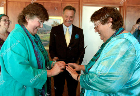 Ann, right, and Michelle Beck exchange wedding vows in the governor's office as Gov. Peter Shumlin looks on in Montpelier, Vt. Shumlin kept a campaign promise to the couple who asked him to marry them