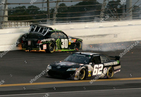 Ricky Carmichael, Michael Annett Nascar driver Ricky Carmichael (30) slides backward out of turn 2 as Michael Annett (62) goes low to avoid the wreck during the Subway Jalapeno 250 auto race in the Nationwide Series at Daytona International Speedway in Daytona Beach, Fla