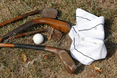 Old wooden clubs, a towel and PH Gutta Percha golf ball lie on the ground at the Oakhurst Links golf course in White Sulphur Springs, W.Va. Oakhurst Links, one of the nation's first golf courses, hopes to find a buyer at auction의 스톡 이미지