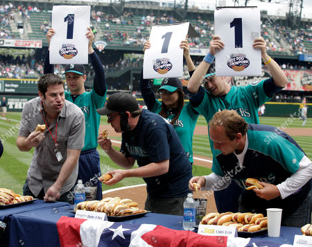 Mike Salk, Danny O'Neil, Chris Egan ESPN radio's Mike Salk, left, Seattle Times sportswriter Danny O'Neil, center, and KING5 TV's Chris Egan, right, take part in a Fouth of July weekend hot dog eating contest for media members prior to an interleague baseball game between the Seattle Mariners and the San Diego Padres, in Seattle