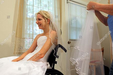 Stock Picture of Rachelle Friedman tries on a veil during the fitting for her wedding dress in Raleigh, N.C. Friedman was left paralyzed after a swimming pool accident that postponed her wedding plans. Now, she is all set to commence with those plans