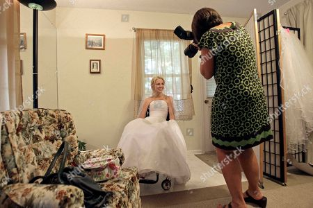 Rachelle Friedman has her photo made by wedding photographer Martha Manning during the fitting for her wedding dress in Raleigh, N.C. Friedman was left paralyzed after a swimming pool accident that postponed her wedding plans. Now, she is all set to commence with those plans