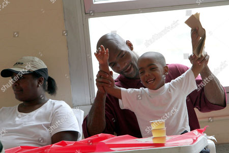Hakim Edwards spends time with his son Mikah Edwards, 4 and his wife Mary Kelly during his graduation ceremony at Sing Sing Correctional Facility, in Ossining, N.Y. More than 50 inmates at New York's Sing Sing prison have graduated from in-house courses designed to help them be better husbands and fathers both during their prison terms and after they're released