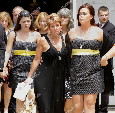 Cheryl Ruggiero, center, the mother of U.S. Army Sgt. Matthew R. Gallagher, and his wife Katie Hall Gallagher, right, lead a procession of mourners out of St. Elizabeth Seton Catholic Church in North Falmouth, Mass., . Gallagher was serving in support of Operation New Dawn in Iraq and died of non-combat related injuries