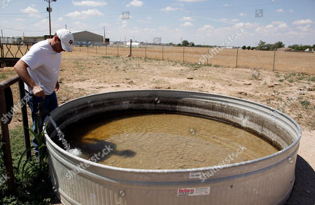 Ranch owner Brad Williams, who has sold half of his cattle due to drought, turns water on for his cattle at a ranch in Canyon, Texas, . After enduring nearly a year of drought, Texans have grown accustomed to seeing acres of withered crops, scores of dried-up ponds and mile after mile of cracked earth