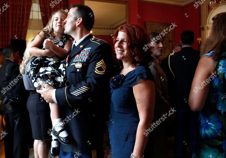 """Stock Image of Ryan Ahern, Gina Ahern Rhianne Ahern, 4, is kissed by her father, Sgt. 1st Class Ryan Ahern, next to his wife Gina Ahern, after he and 5 other members of the U.S. Special Forces were presented the French """"Croix de la Valeur militaire"""" for distinguished service in Afghanistan alongside the French Taskforce La Fayette, during a ceremony at the Residence of France in Washington, on"""