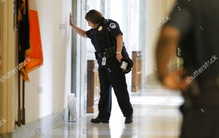 A Capitol Police officer, left, looks at an unattended package near the office of Rep. Anthony Weiner, D-N.Y, on Capitol Hill in Washington. The unattended package prompted an evacuation of the area