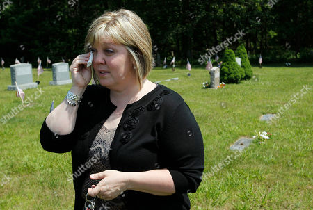 Patty Tsouvalos, of Woonsocket, R.I., mother of murdered 17-year-old Brandon Smith, wipes a tear from her eye while speaking with a reporter at the Union Cemetery, in North Smithfield, R.I. Smith was ambushed as he was returning home from a convenience store on June 25, 2008 by a gunman who was lying in wait, his mother said. Smith is buried near relatives in the cemetery