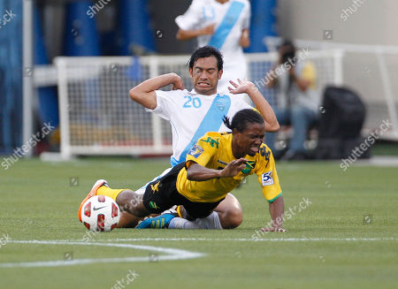 Stock Image of Jason Morrison, Carlos Ruiz Jamaica's Jason Morrison, front, falls to the ground in front of Guatemala's Carlos Ruiz (20) in the first half of a CONCACAF Gold Cup soccer match, in Miami
