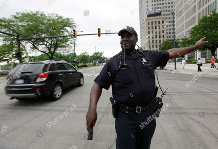 Stock Image of Detroit Police officer Carlos Griffin directs traffic at Woodward and Jefferson Avenues with traffic lights not working downtown in Detroit, . Sections of downtown Detroit lost power Thursday afternoon after high demand for energy caused the city's municipal power system to have a major failure, city officials said. The outage forced the evacuation of the Coleman Young Municipal Center, the McNamara federal building, the county courthouse, Cobo Center and some schools. The outages were spotty - traffic lights were out in certain areas but working in other parts of the downtown district