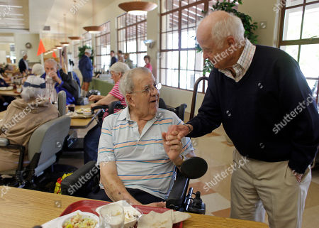 Sunday, April, 17, 2011, John Shafer, right, chairman of Shafer Vineyards, visits with veteran Harry Chiarello, left, father of celebrity chef Michael Chiarello, during a lunch at the Veterans Home of California in Yountville, Calif. The lunch included a program called Vintners for Veterans which provides high-quality wines to the men and women at the home to be enjoyed with their Sunday meal