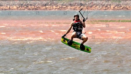 Stephen Taylor, of Oklahoma City, performs a jump on his kite board at Lake Hefner In Oklahoma City, . Due to drought in the state, lake levels are extremely low, as seen in the red dirt at rear, which is usually covered by lake water. Thanks to a late-spring heat wave, highs have been in the 90s or low triple digits for nearly a week in much of the state