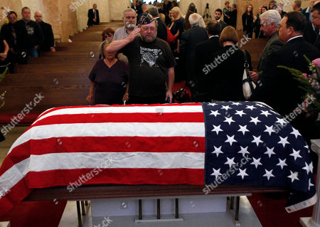 """Vietnam veteran Spike Tyson, of Lansing, salutes the casket of Dr. Jack Kevorkian at a public memorial in Troy, Mich., . Friends, family and supporters of the late Dr. Jack Kevorkian have paid tribute to the polarizing assisted-suicide advocate during a public memorial service in suburban Detroit. Kevorkian will be laid to rest later Friday during a private grave-site service for those closest to him. He died in a hospital last week at age 83. Kevorkian was an advocate of allowing health care professionals help gravely-ill people die and he claimed he assisted in about 130 deaths. He spent eight years in prison for second-degree murder after """"60 Minutes"""" broadcast video of him helping someone die in 1998"""