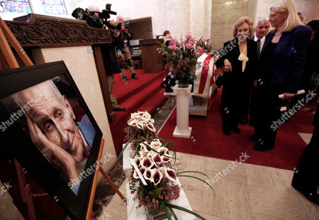 """Mourners pay their respects at Dr. Jack Kevorkian's casket during a public memorial in Troy, Mich., . Friends, family and supporters of the late Dr. Jack Kevorkian have paid tribute to the polarizing assisted-suicide advocate during a public memorial service in suburban Detroit. Kevorkian will be laid to rest later Friday during a private grave-site service for those closest to him. He died in a hospital last week at age 83. Kevorkian was an advocate of allowing health care professionals help gravely-ill people die and he claimed he assisted in about 130 deaths. He spent eight years in prison for second-degree murder after """"60 Minutes"""" broadcast video of him helping someone die in 1998"""