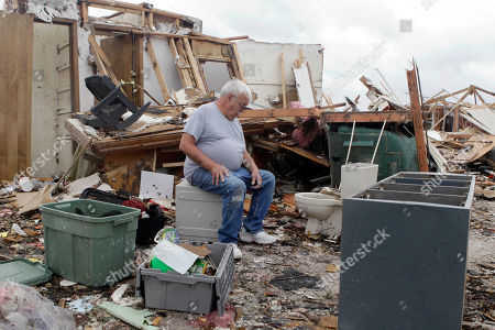 Kenneth Thomas sits on a safe in what was his living room, in Joplin, Mo. Thomas took shelter with his wife, Retha, in a bathroom located directly behind where he is seated when a massive tornado struck Joplin Sunday night. Both escaped with only minor injuries
