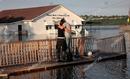 Lauren Lucas is comforted by her husband David Lucas, as they stand on a broken deck and watch her mother's business, the Vidalia Dock and Storage, take on floodwaters from the Mississippi River in Vidalia, La