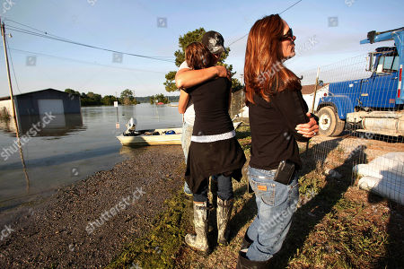 Carla Jenkins, right, owner of Vidalia Dock and Storage, cries, while her daughter Lauren Lucas, left, is hugged by her husband David Lucas, while they survey the damage to her business as floodwaters from the rising Mississippi flood the buildings, in Vidalia, La