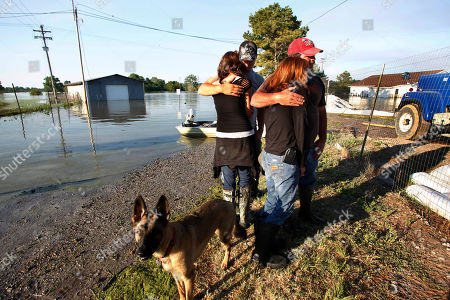Carla Jenkins, second right, owner of Vidalia Dock and Storage, is hugged by Port Captain Travis Morace, while her daughter Lauren Lucas, left, is hugged by her husband David Lucas, while they survey the damage to her business as floodwaters from the rising Mississippi flood the buildings, in Vidalia, La