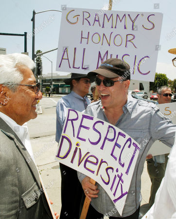 Oscar hernandez, right, two-time Grammy winner for Best Latin jazz Album in 2005 and 2011, chats with Pete Escovedo as musicians and others demonstrate outside a meeting of the board of the National Academy of Recording Arts and Sciences, demanding restoration of more than 30 categories cut from the Grammy Awards, at the Beverly Hilton Hotel in Beverly Hills, Calif., . They say the reductions unfairly target ethnic music and were done without the input of the academy's thousands of members