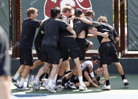 Ray Sarmiento, Daniel Nguyen Southern California tennis player Daniel Nguyen, bottom, is smothered by Ray Sarmiento as they are surrounded by teammates after defeating Virginia in the finals of the NCAA college tennis championships in Stanford, Calif., . USC defeated Virginia 4-3