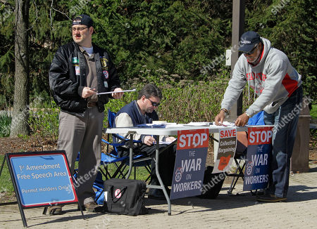 Teamsters Matt Ford, left, Eric McKee, center, and Charles Smith collect signatures on petitions to repeal Ohio's collective bargaining law outside the Cleveland Metroparks Zoo, in Cleveland