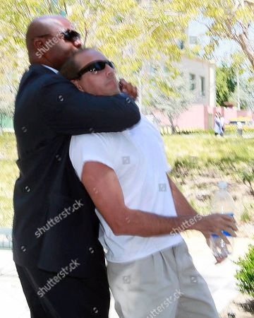 One of Paris Hilton's bodyguards, left, restrains an unidentified assailant after the man grabbed Paris Hilton's boyfriend Cy Waits as Waits and Hilton were walking into court in Los Angeles. The assailant was detained by police