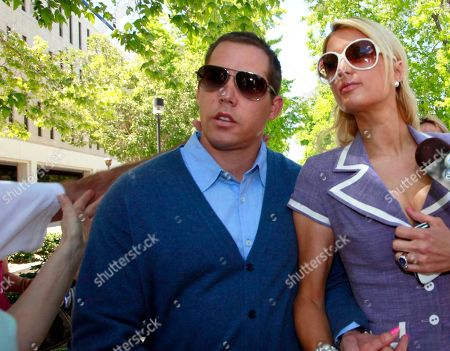 Cy Waits, Paris Hilton An unidentified assailant's arm is shown at left reaching out to grab Cy Wait, left, as he and Paris Hilton walk towards court in Los Angeles. After grabbing Waits the assailant was restrained by Hilton's bodyguard and later detained by police