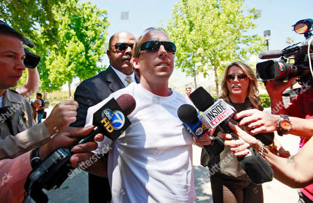 One of Paris Hilton's bodyguards, rear, escorts an unidentified assailant after the man grabbed Paris Hilton boyfriend Cy Waits while Waits and Hilton were walking into court in Los Angeles