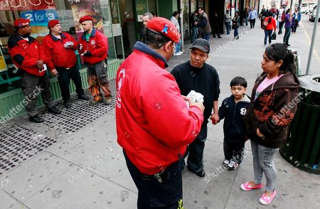 Benjamin Garcia, Abraham Cinto, Rosaura Morales, Erik Martinez Benjamin Garcia, center, patrol director with the Guardian Angels, talks to Abraham Cinto, center right, and his wife Rosaura Morales, right, about the patrol services of the Angels as the family strolled through downtown Paterson with their 5-year-old son Erik Martinez, in Paterson, N.J. Eighteen Guardian Angels began patrolling the city on April 17 per an invitation from Paterson Mayor Jeffery Jones. On Monday, the Paterson Police Department laid off 125 officers, which is a quarter of the police force