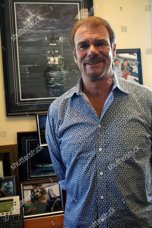 May 24, 2011, Tom Alexander poses for a photo in his real estate office in Anchorage, Alaska. Alexander and four others survived the sinking of a pleasure boat, near Kodiak Island, Alaska