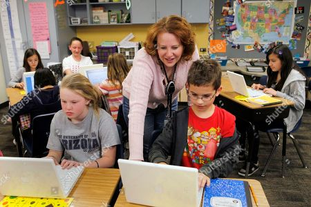 High Plains Elementary School teacher Jennifer Williford, center, works with Colette Jackson, 11, and Skyler Matteson, 10, right, on a computer project in her fifth grade class at the school in Englewood, Colo. Colorado has long debated the standardized tests it gives schoolchildren. Now state officials are talking about a dramatic answer to standardized tests in many grades _ none of the above. State lawmakers are expected to consider joining other states in turning away from testing requirements except for those required by the federal government