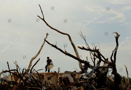 Phillip Bailey salvages belongings from a friend's devastated Joplin, Mo. home . An EF-5 tornado tore through much of the city Sunday, damaging a hospital and hundreds of homes and businesses and killing at least 126 people