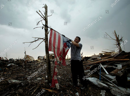 Kerry Roberts removes a tattered flag from a pole so he can fold and destroy it in a devastated Joplin, Mo. neighborhood . An EF-5 tornado tore through much of the city Sunday, damaging a hospital and hundreds of homes and businesses and killing at least 126 people