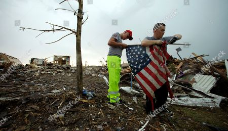 Stock Image of Kerry Roberts, right, and Keegan Spurlin, both from Houston, Mo., remove a tattered flag from a pole so they can fold and destroy it in a devastated Joplin, Mo. neighborhood . An EF-5 tornado tore through much of the city Sunday, damaging a hospital and hundreds of homes and businesses and killing at least 126 people