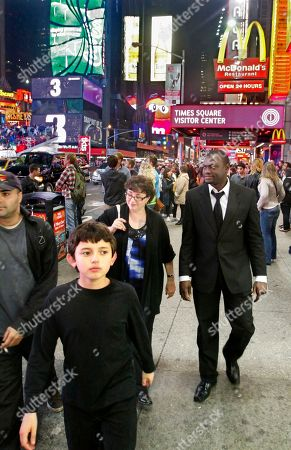 """Nelson Hebo Jane Cormier, center, and her son Christopher Martinez, 10, foreground, walk with Angolan tenor Nelson Hebo to their hotel in Times Square following his performance at Carnegie Hall for the winners of the 2011 Gerda Lissner Foundation International Vocal Competition in New York. Nelson, who calls Cormier and her family his """"adopted"""" family, met Cormier in 2008 when he preformed in her opera company in Alton, N.H"""