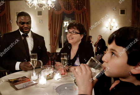 """Nelson Hebo Jane Cormier, center, and her son Christopher Martinez, 10, join Angolan tenor Nelson Hebo at a reception in New York following his performance at Carnegie Hall for the winners of the 2011 Gerda Lissner Foundation International Vocal Competition. Nelson met Cormier in 2008 when he preformed in her opera company in Alton, N.H., and now calls her family in New Hampshire his """"adopted"""" family. Nelson rarely talks about Angola, or the many family members who have died, including his parents, confiding in just a few people - a priest, and Cormier's family of opera singers who have embraced Nelson as one of their own"""