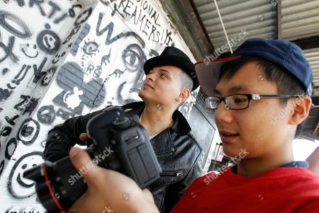 """Stock Image of Lil Eddie Serrano This photo shows photographer Jason Chee, right, as he checks his images on the back of his camera after photographing """"Lil Eddie Serrano,"""" during the recording of Serrano's music video against the backdrop of a wall painted by Whitney Museum teens beneath section 1 of the High Line in New York. The ribbon was cut Tuesday, June 7 on the long-awaited second section of the High Line. The new section ends at 30th Street, adding nine blocks and doubling the length to one mile. The first segment opened in June 2009 and runs from Gansevoort Street to 20th Street"""