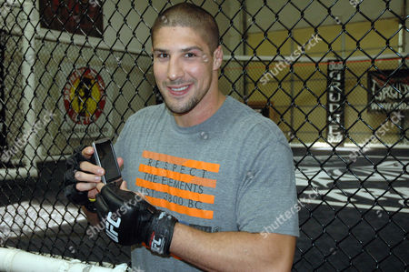 This photo made shows UFC heavyweight Brendan Schaub posing with his phone before a workout at the Grudge Training Center in Wheat Ridge, Colo. Schaub embraces social media and has more than 20,000 followers on twitter