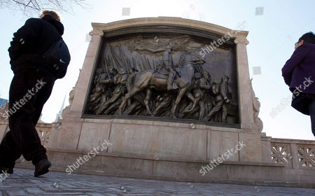 """People walk past the memorial to Union Col. Robert Gould Shaw and the 54th Massachusetts Volunteer Infantry Regiment, near the Statehouse in Boston. The 54th was the first regiment composed of men of African decent recruited in the North for battle in the Civil War. The National Gallery of Art in Washington has organized the exhibition """"Tell it with Pride,"""" opening, to explore the black soldiers honored in the Shaw Memorial"""