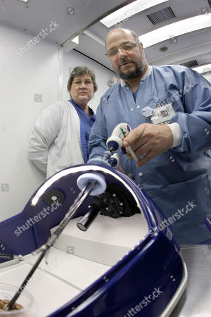 St. Joseph's Mercy Health Center surgical technician Mel Salvatori, right, manipulates laparoscopic surgical tools through a simulated belly button in a training device as Dallas Smith R.N. looks on in Hot Springs, Ark