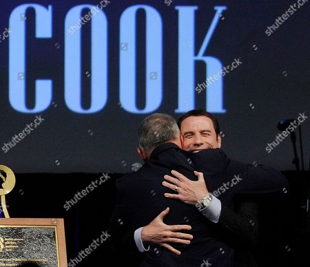 "John Travolta, Dick Cook Actor John Travolta, facing camera, embraces former Walt Disney Studios chairman Dick Cook before awarding him the ""Pioneer of the Year"" award during a dinner at CinemaCon 2011, in Las Vegas"