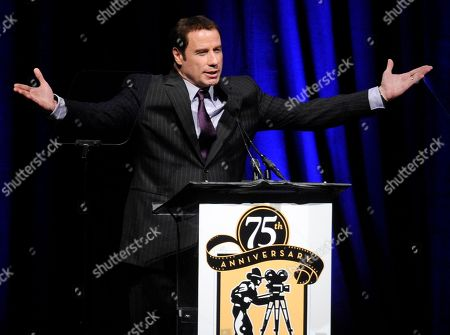 """John Travolta Actor John Travolta appears onstage to present the """"Pioneer of the Year"""" award to former Walt Disney Studios chairman Dick Cook during the Pioneer of the Year Dinner at CinemaCon 2011, in Las Vegas"""