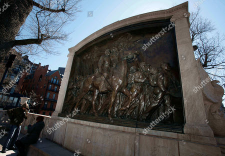 People sit beside the memorial to Union Col. Robert Gould Shaw and the 54th Massachusetts Volunteer Infantry Regiment, near the Statehouse in Boston. The 54th was the first regiment composed of men of African decent recruited in the North for battle in the Civil War