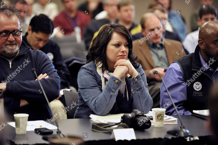 April Walker, center, is shown at one of the daily flood briefings in Fargo, N.D., during the flooding of the Red River. Walker, who was born and raised in North Dakota, is the city's storm sewer utility engineer which means she manages high water for a living. Fargo has faced serious floods in four of her first five years on the job
